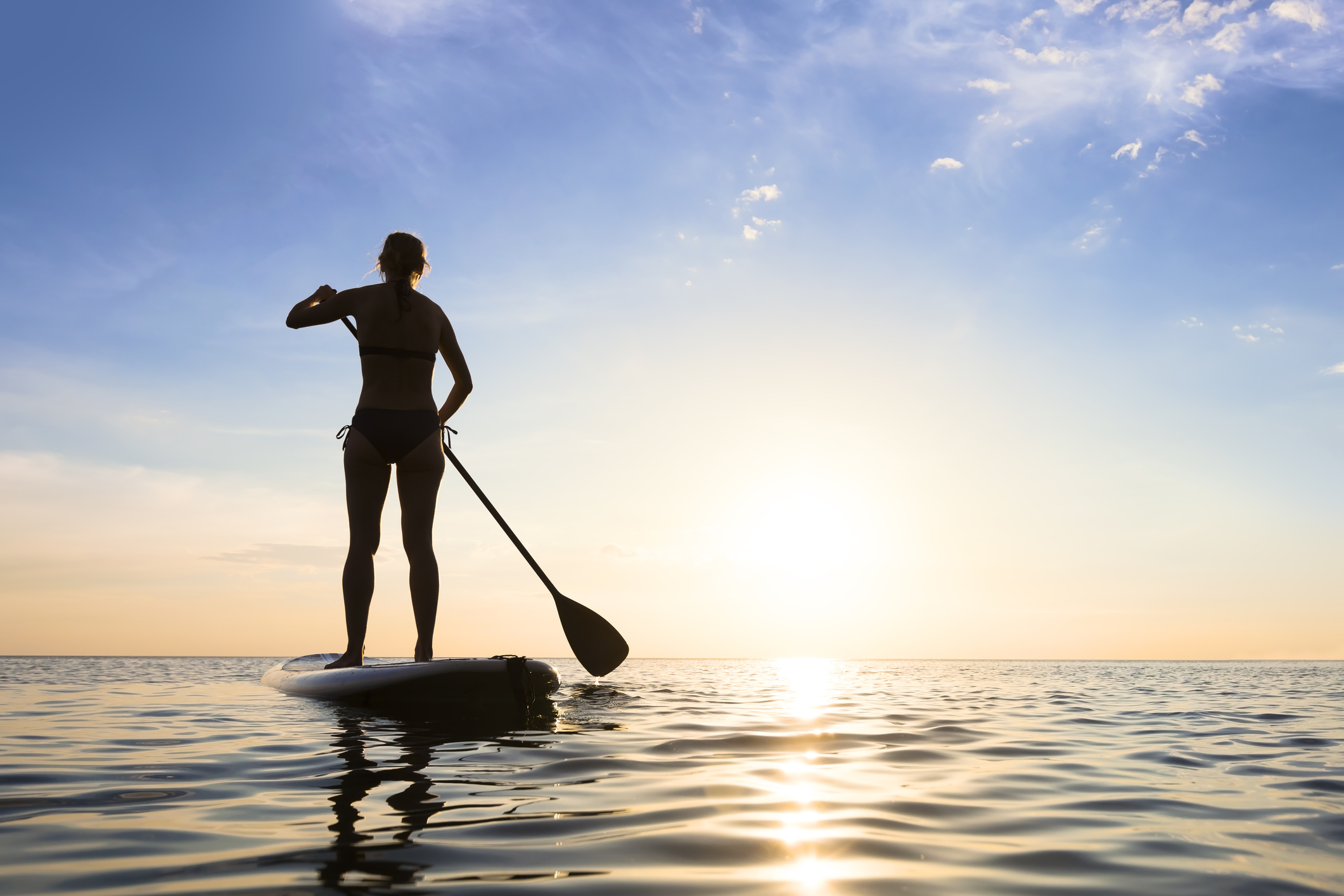 Girl Stand Up Paddle Boarding (sup) On Quiet Sea At Sunset